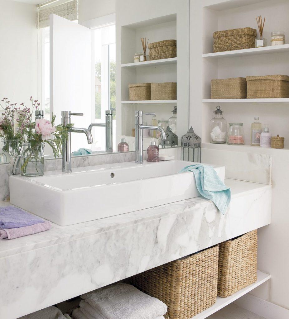 Lavabo con encimera empotrada de mármol y cestos debajo