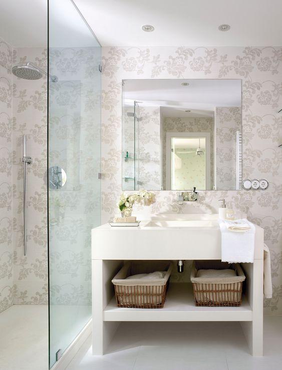 Baño con papel pintado en tonos claros incluso en la zona de ducha