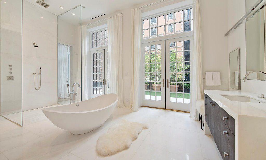 Amplio baño de mármol con ventanales de Jennifer López