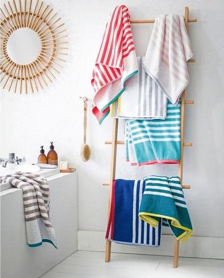 Baño con espejo sol de bambú y toallas de colores