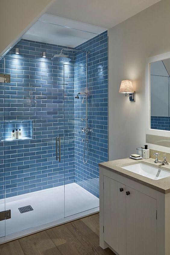 FIjo de ducha con plato blanco y azulejos azules