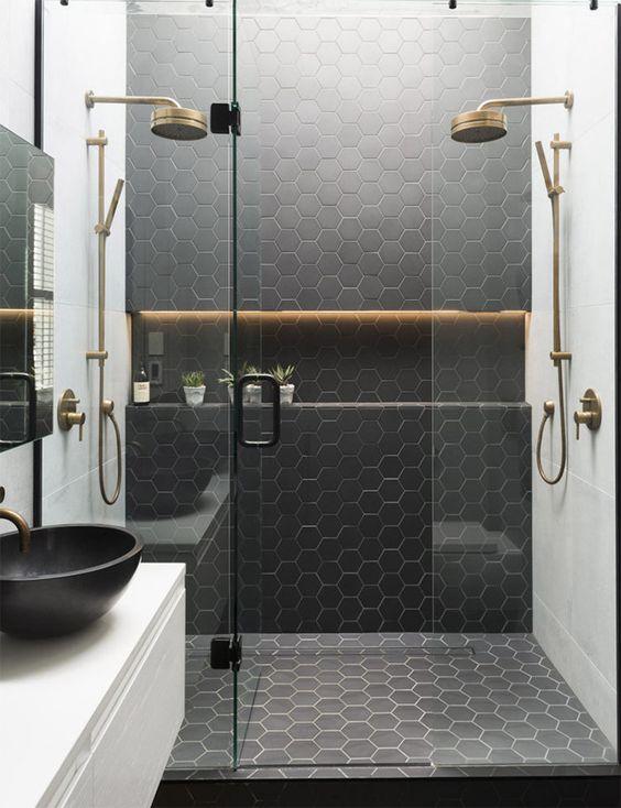 Espacio de ducha con baldosas negras, mampara transparente y grifería vintage