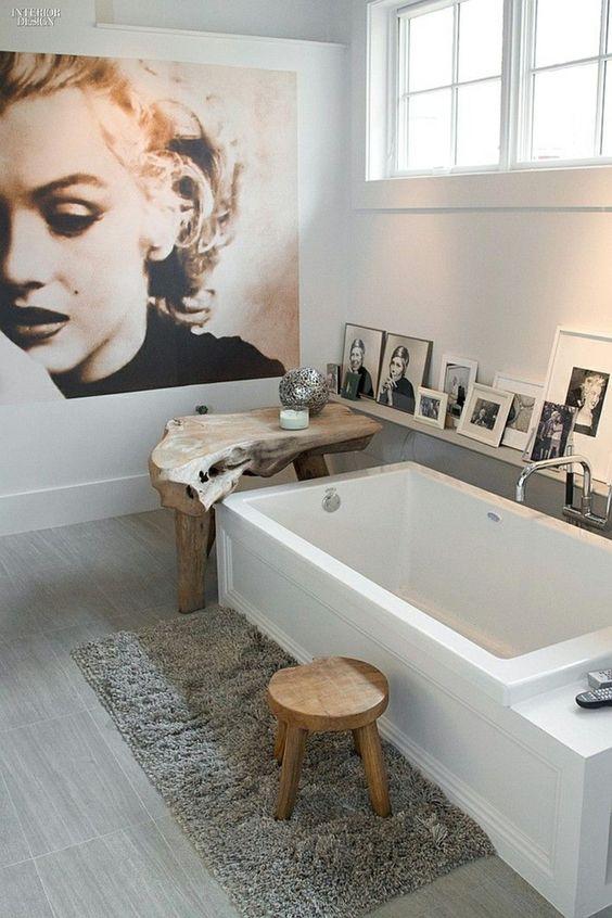Baño con fotos junto a la bañera y cuadro grande