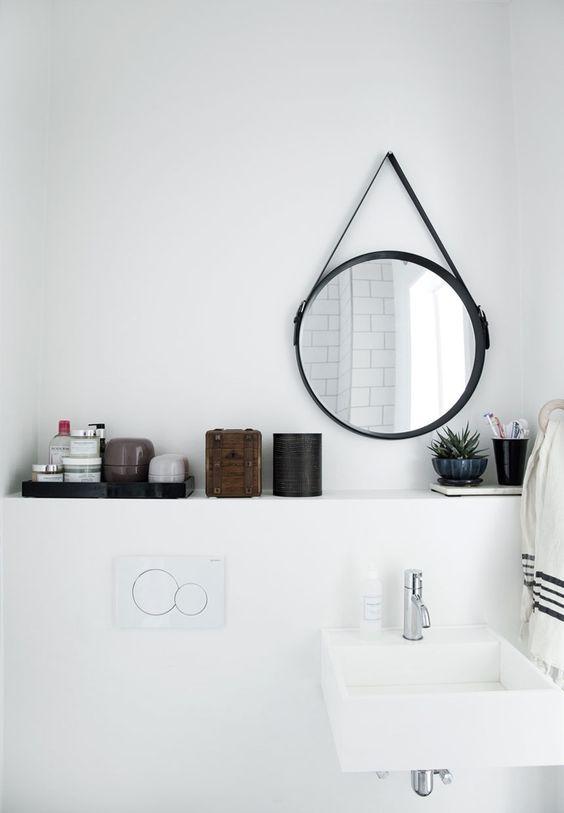Espejo redondo de metal negro en baño blanco de estilo nórdico