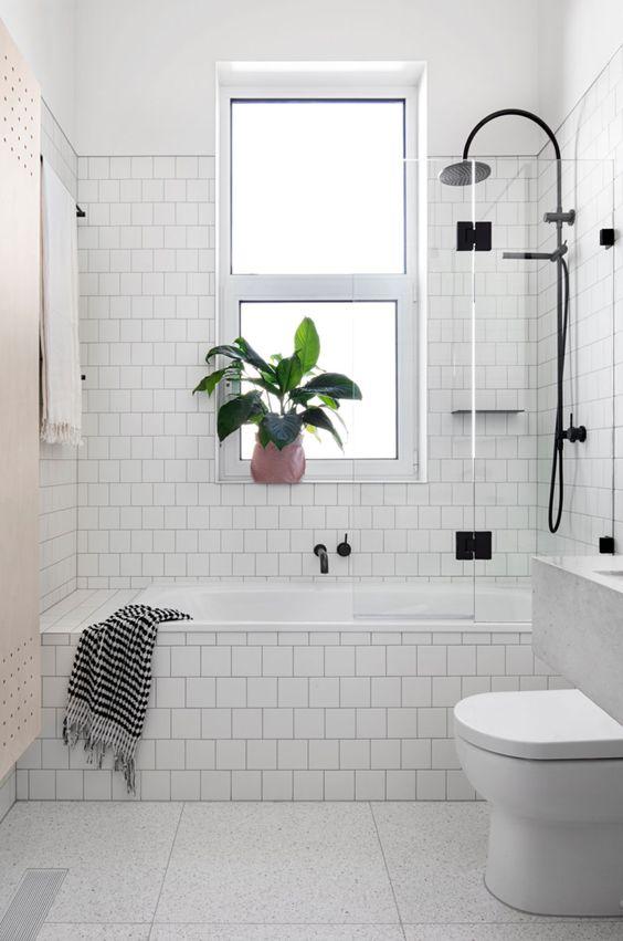 Baño nórdico con azulejos blancos y mampara industrial
