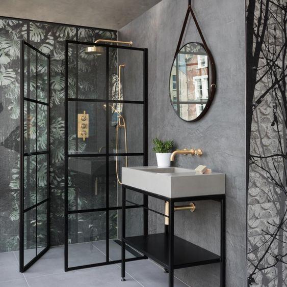 Baño industrial con mampara de perfil negro y espejo redondo con borde negro