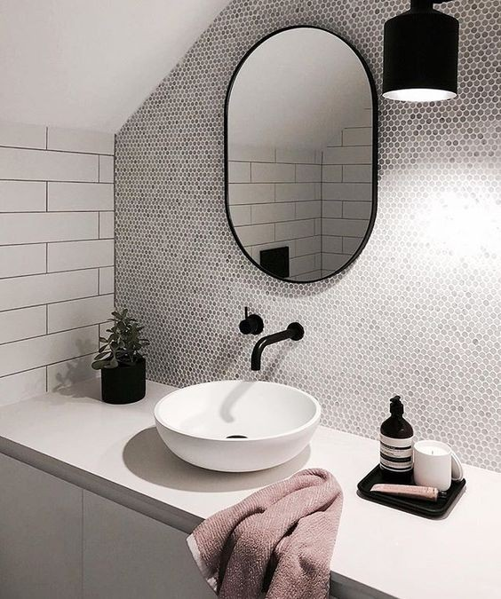 Tocador de baño de estilo industrial con grifos en negro y espejo ovalado